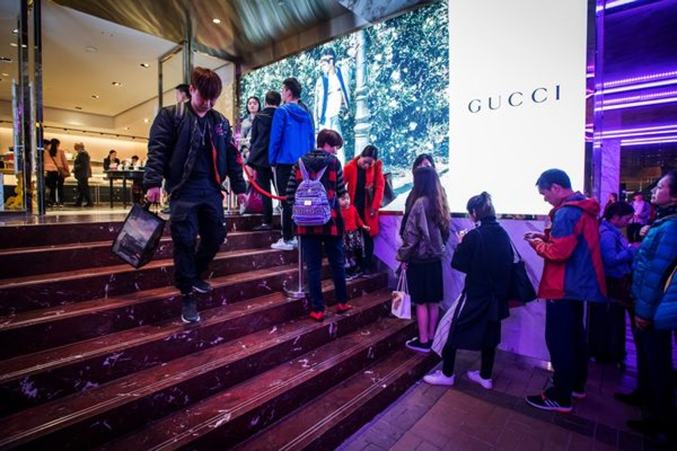 Shoppers wait in line at a Gucci store in Hong Kong. Photo: Bloomberg