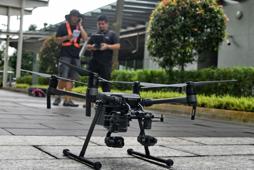Staff members of Singapore technology firm H3 Dynamics preparing to fly a drone to inspect a building facade in Singapore. Image: AFP