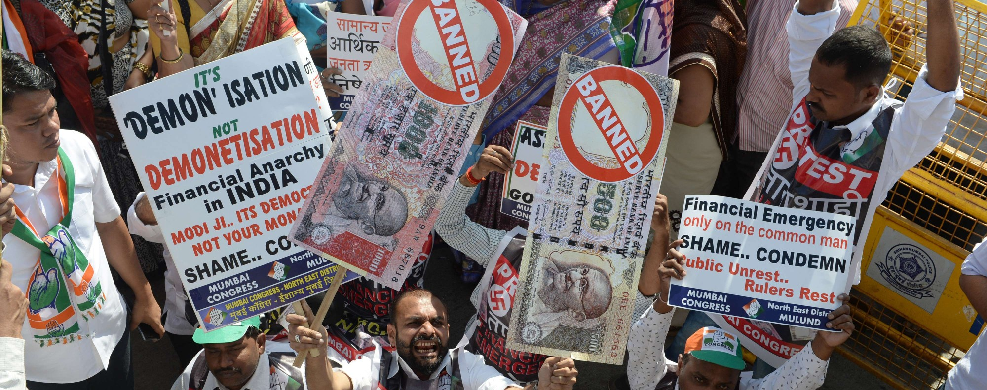 "An Indian protestor holds placards of banned 500 and 1000 rupee notes during a protest against demonetisation, in Mumbai on November 28, 2016. Tens of thousands of people turned out November 28, for nationwide protests against India's controversial ban on high-value banknotes, which opposition party organisers say has caused a ""financial emergency"". / AFP PHOTO / INDRANIL MUKHERJEE"