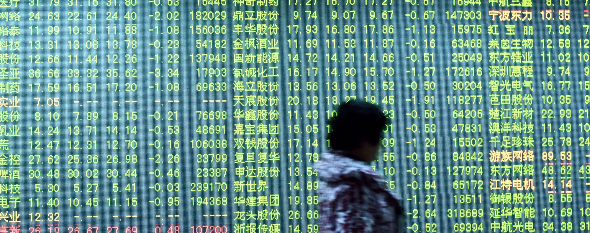 (FILES) This file photo taken on January 11, 2016 shows an investor walking past a screen showing stock market movements at a securities firm in Hangzhou in eastern China's Zhejiang province. China is the world's second-largest economy and has one of the fastest growth rates of any G20 nation, but its stock markets have been among the worst performing in the world this year. / AFP PHOTO / STR / China OUT / TO GO WITH China economy stocks, FOCUS by Albee ZHANG