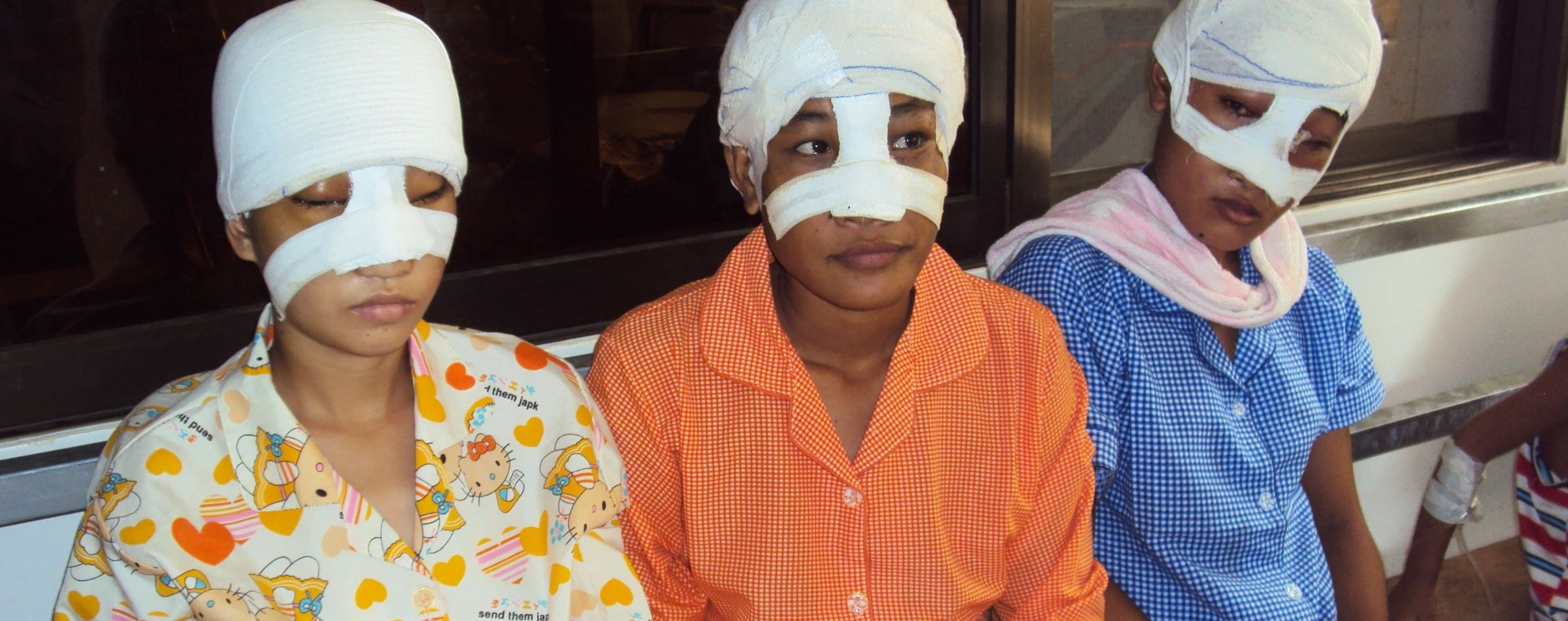 Three Cambodian teenagers after surgery to remove facial disfigurements.