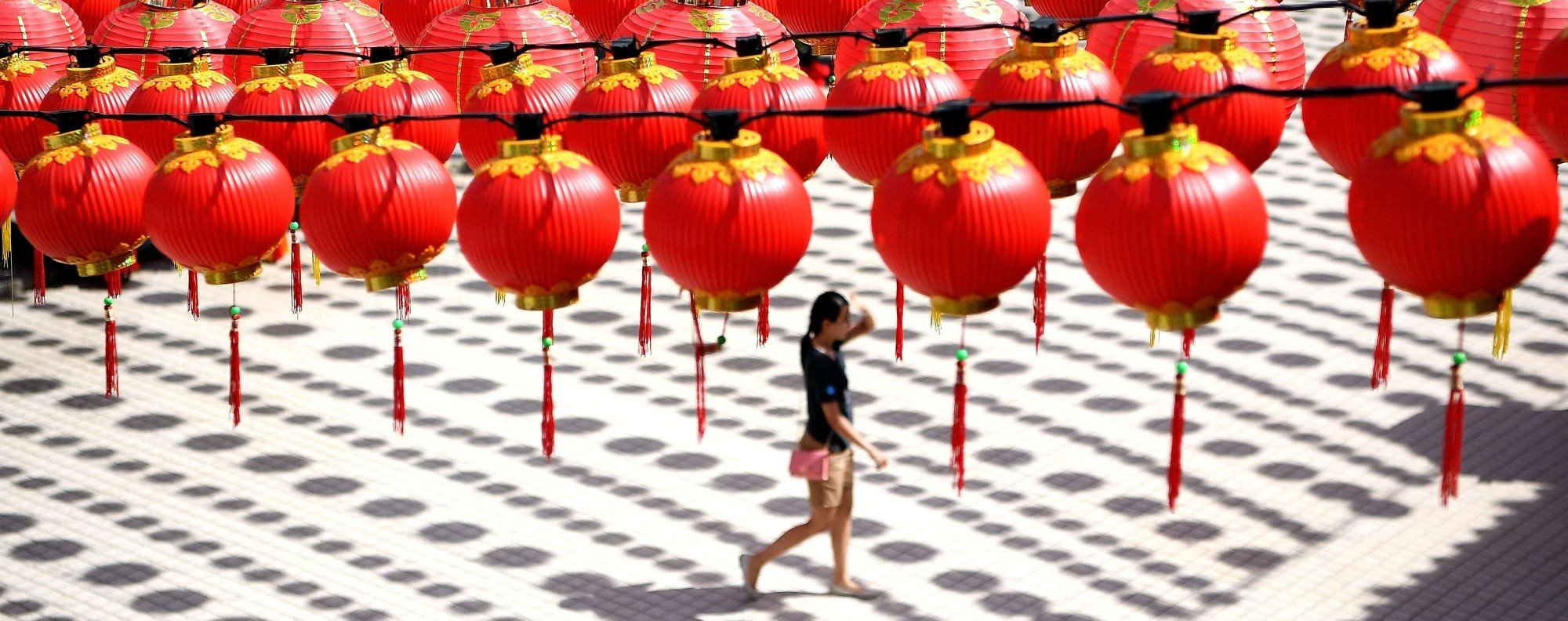 A woman walks under traditional Chinese lanterns in Kuala Lumpur. Photo: AFP