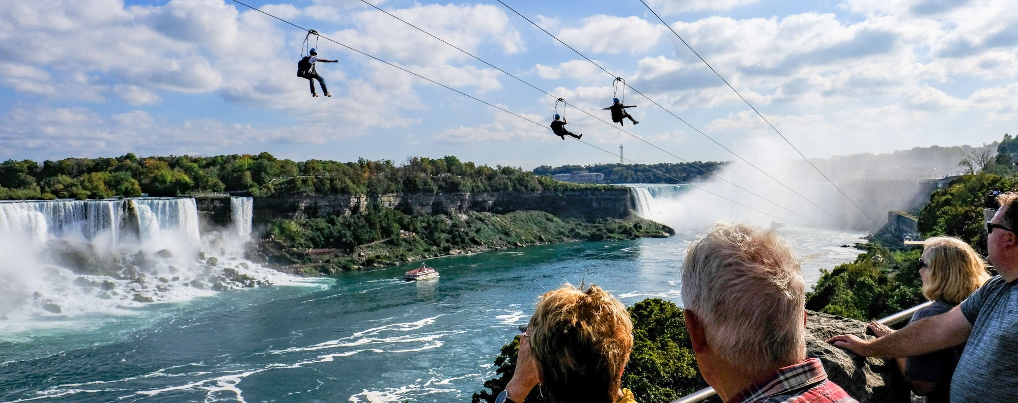 Tourists glide by zip line over Niagara Falls.