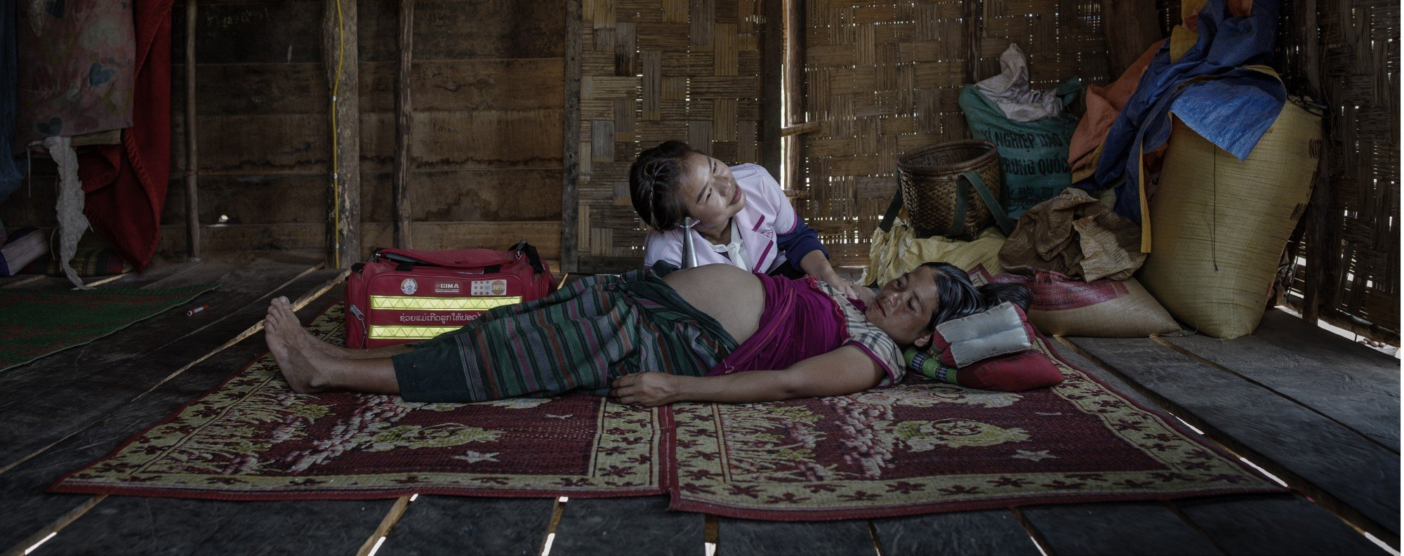 Midwife Phanmaha Nongthilath examines pregnant Chien in Asing Saneh, Laos.