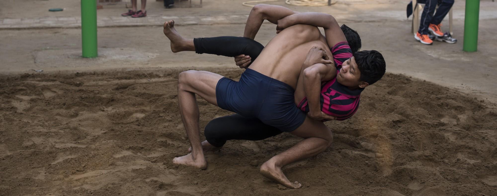 Neha Kumari wrestles a male opponent in an akhara in Delhi.