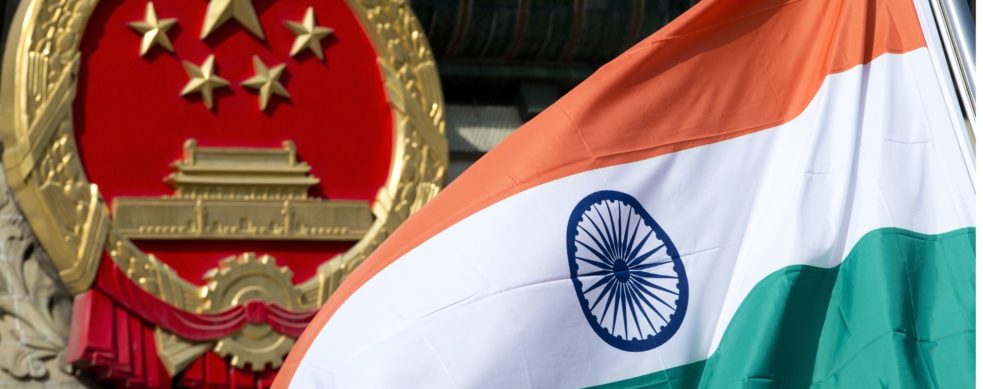 An Indian national flag and a Chinese national emblem. Photo: AP