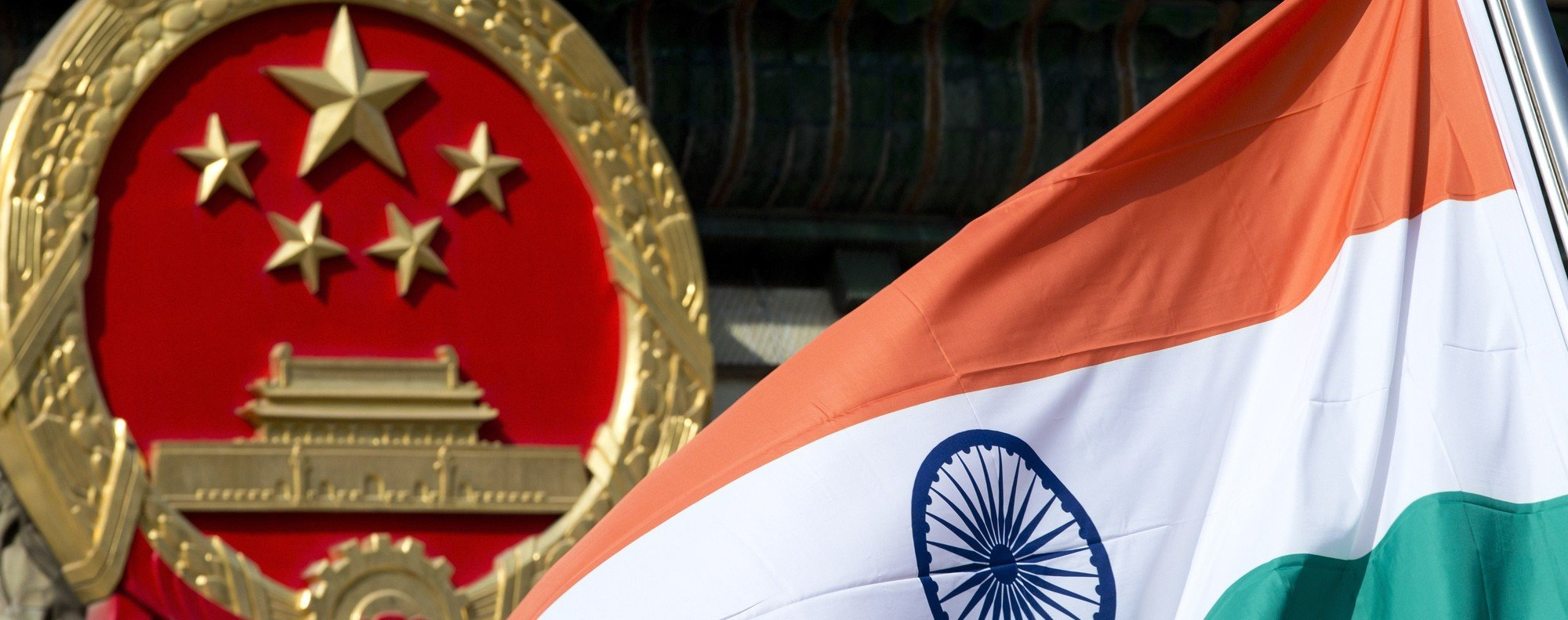 An Indian national flag flies next to the Chinese national emblem. Photo: AP