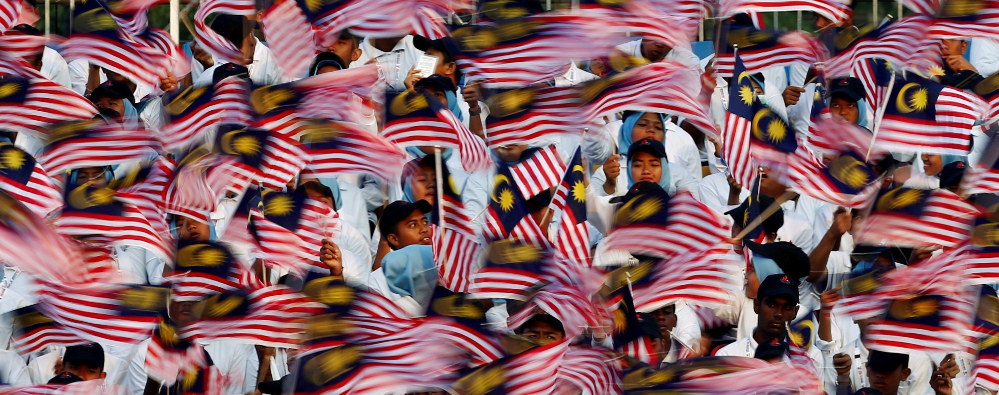 Performers wave Malaysian flags. Photo: Reuters