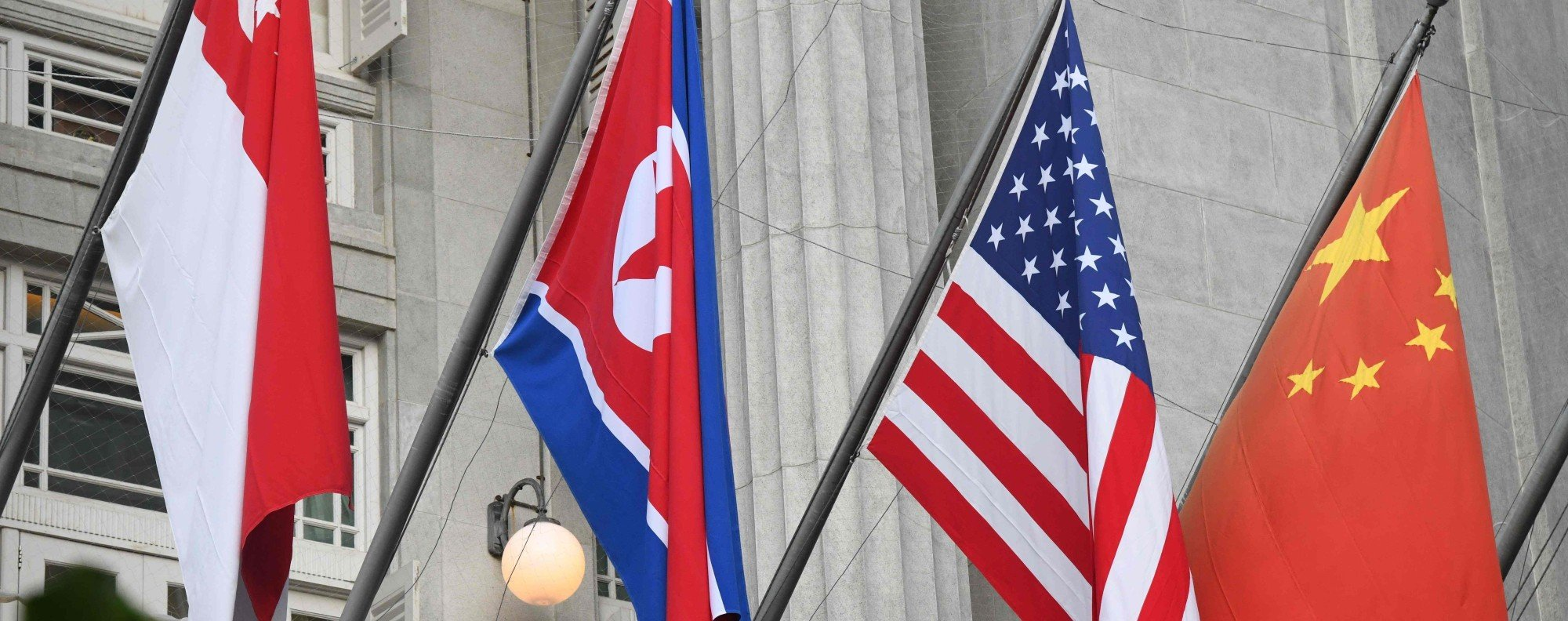 North Korean flag is seen along side the US, China and Singapore flags at the facade of the Fullerton hotel in Singapore. Photo: AFP