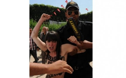A Tunisian security guard arrests one of three Femen activists protesting in front of the Ministry of Justice in Tunis. Photo: EPA