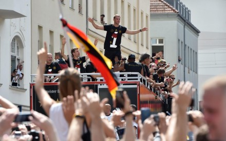 """Germany goalkeeper Manuel Neuer gestures to fans during the drive along the so-called """"Fan Meile"""" at Brandenburg Gate in Berlin on Tuesday. Photo: EPA"""