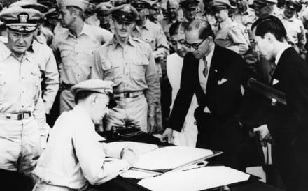 Japanese foreign minister Mamoru Shigemitsu watches as Lieutenant General Richard K. Sutherland signs the surrender document at the end of the Pacific war, on September 2, 1945, aboard the USS Missouri, in Tokyo Bay.