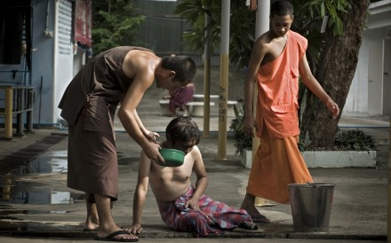 A monk comforts a patient who has taken the detox medicine. At Wat Thamkrabok, everyone vomits. Photos: AFP; Nathan Thompson