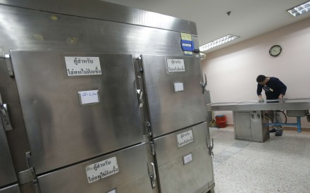 A Thai man convicted of drunk drinking cleans an autopsy table at Taksin Hospital in Bangkok. Photo: AP