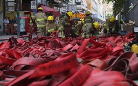 Firemen clean up after extinguishing the Ngau Tau Kok blaze that burned for more than 108 hours. Photo: Sam Tsang