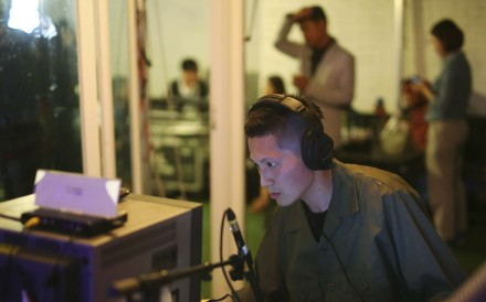 """Hong Kong sound artist Samson Young performs his work """"Nocturne"""" in Seoul, in which the recreated sounds of war are broadcast to the audience on hand-held radios. Photo: SCMP Pictures"""