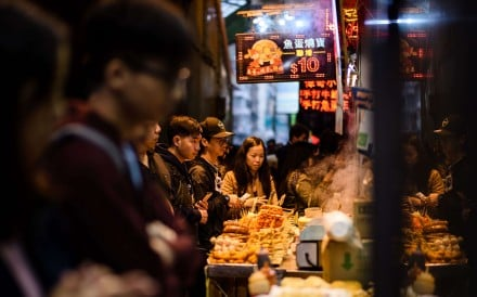 Customers queue to buy snacks being sold by food vendors. Photo: AFP Photo