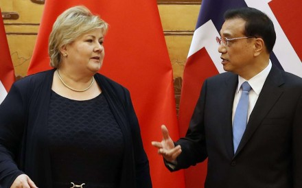 Chinese Premier Li Keqiang speaks to Norwegian Prime Minister Erna Solberg as they attend a signing ceremony at the Great Hall of People in Beijing on Thursday. Photo: EPA