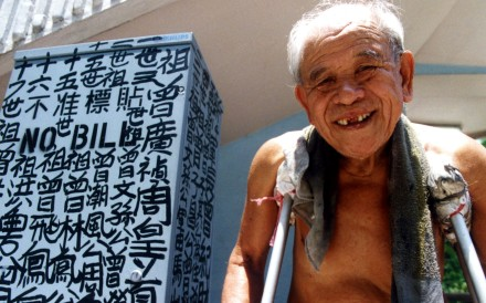 The self-appointed King of Kowloon, Tsang Tsou-choi, next to one of his works. Photo: courtesy of Birdy Chu