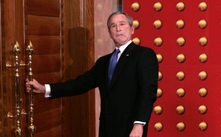 George W. Bush jokingly makes a face as he tries to open a locked door as he leaves a press conference in Beijing in 2005. File photo: AP