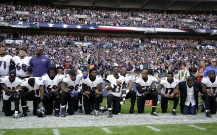 Baltimore Ravens players, and former player Ray Lewis, second from right, kneel during the playing of the US national anthem before an NFL football game against the Jacksonville Jaguars at Wembley Stadium in London, on Sunday. Photo: AP