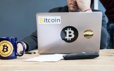 Un dipendente utilizza un computer portatile con Bitcoin loghi di marca all'interno degli uffici di una banca in Francia. Foto: Bloomberg