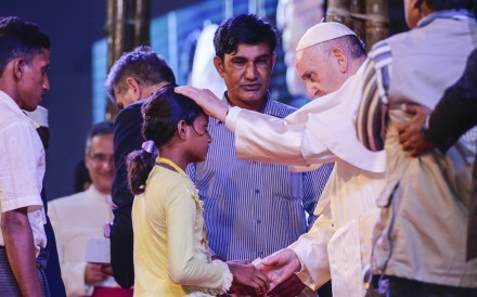 Pope Francis consoles a Rohingya orphan girl during a meeting at the garden of the Archbishop in Dhaka, Bangladesh. Photo: EPA