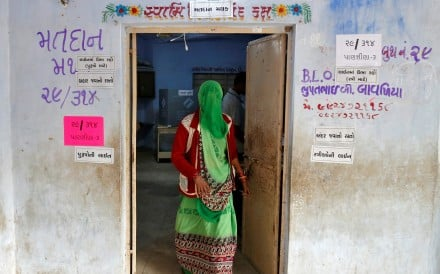 A woman leaves a polling booth after casting her vote during the first phase of Gujarat state assembly election in Panshina village of Surendranagar. Photo: Reuters