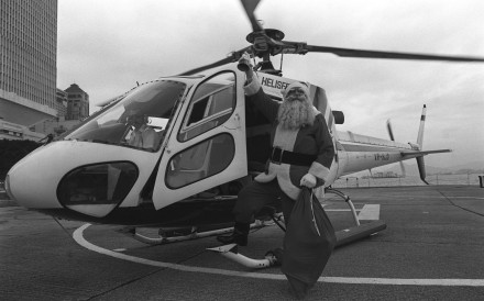 A man dressed in a Santa Claus outfit arrives by helicopter to distribute gifts at an event in Edinburgh Place, Central.
