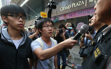 Scholarism convenor Joshua Wong Chi-fung (left) and Raphael Wong Ho-ming (centre) of the League of Social Democrats at a clearance operation at Mong Kok occupied site. Photo: K.Y. Cheng
