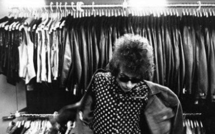 A young Bob Dylan, sporting his trademark Ray-Ban Wayfarer sunglasses, puts on a jacket to add to his iconic look.