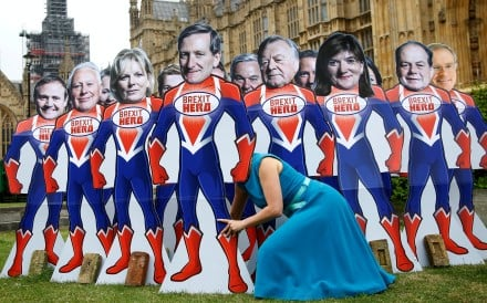 An anti-Brexit campaigner from global activism group Avaaz sets up cardboard cut-outs of Conservative Party MPs, who are known to support remaining in the European Union, outside Parliament in Westminster, London, on June 20. Photo: Reuters