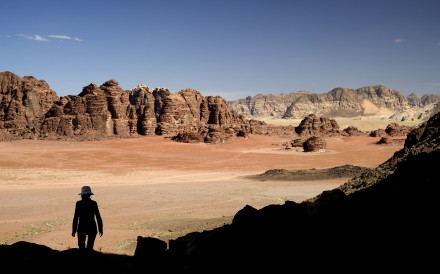 Steep cliffs tower over the red sand desert of Wadi Rum, a sandstone valley in southern Jordan. Photo: Photononstop