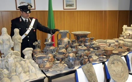 An Italian officer looks at Greek and Roman objects recovered on Wednesday after police dismantled an international ring trafficking ancient artefacts. Photo: Carabinieri Police via AP
