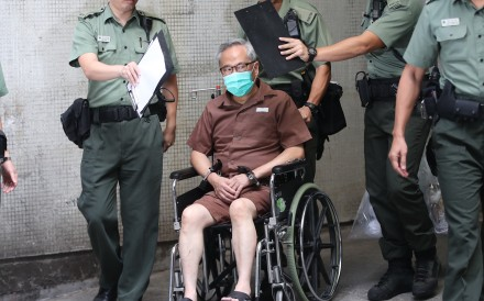 Former chief executive Donald Tsang is escorted by Correctional Services Department officers as he is discharged from hospital. Photo: Edward Wong
