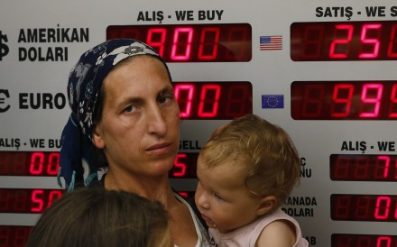 People wait at a currency exchange shop in Istanbul on August 15. The Turkish lira has nosedived in value in the past week, but some Turks are reacting with defiance to their plunging currency and an escalating trade and political dispute with the United States. Photo: AP