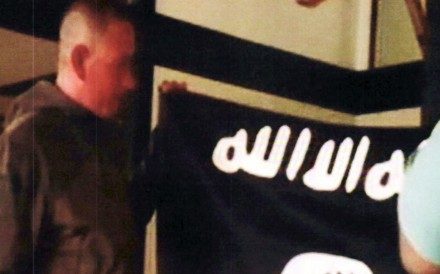 In this July 8, 2017, file image taken from FBI video and provided by the US Attorney's Office in Hawaii, Army Sergeant Ikaika Kang holds an Islamic State group flag after allegedly pledging allegiance to the terror group at a house in Honolulu. Photo: AP
