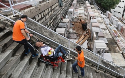 Lee Sau-yee is helped up stairs to his brother's resting place on Tuesday. Photo: Sam Tsang