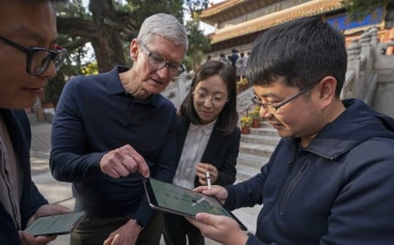 Liu Zhipeng (far right), one of the founders of Xichuangzhu, shows Apple's CEO Tim Cook (second left) how to write calligraphy on an iPad with Apple Pencil at the Beijing Confucian Temple on Wednesday. During his stay in China Cook also visited Bytedance. Photo: Xinhua