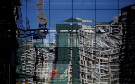 A construction site and residential building reflected on the glass wall of a building in Beijing. Photo: Reuters