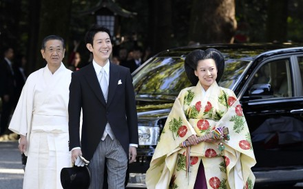 Japanese Princess Ayako, the third daughter of the late Prince Takamado, dressed in traditional ceremonial gown, and Japanese businessman Kei Moriya arrive at Meiji Shrine for their wedding. Photo: Kyodo