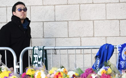 Aiyawatt Srivaddhanaprabha, the son of Leicester City chairman Vichai Srivaddhanaprabha, who died in a helicopter crash at the club's stadium, looks at the floral tributes left to the victims of the crash. Photo: AFP