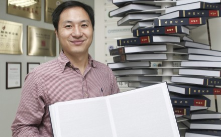 Scientist He Jiankui, who sparked controversy with his announcement that he had altered the genetic material of twin girls before birth, poses with The Human Genome, a book he edited, at his company Direct Genomics in Shenzhen, China, in August 2016. Photo: Reuters
