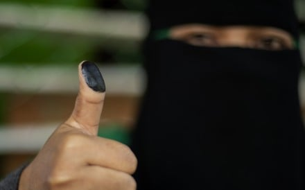 A woman shows her inked thumb after voting in Cotabato City. Photo: AFP