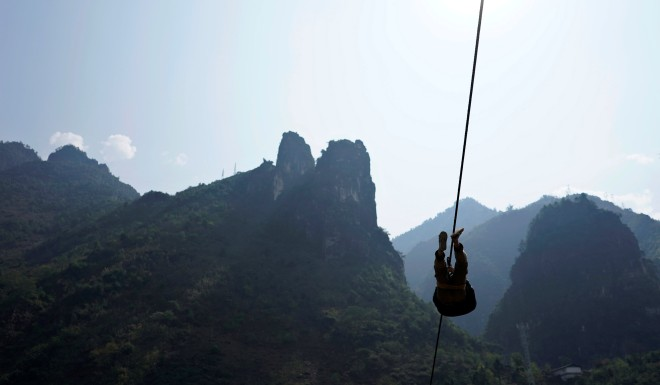 A man of the Lisu ethnic group leaves his mountainside village on a zipline.