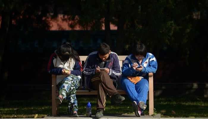 A group of Chinese young people play on their mobile phone as they rest on a bench at a park in Beijing on November 7, 2013. Photo: AFP