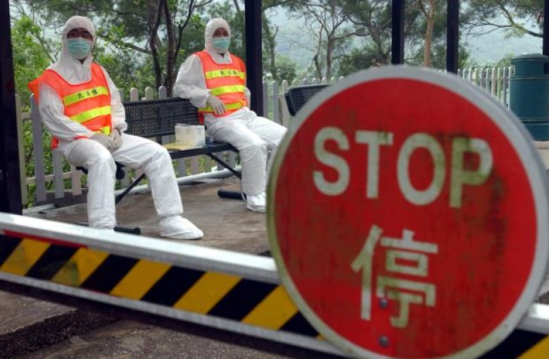 Security officers in protective gear guard a quarantine centre housing residents of Amoy Gardens.