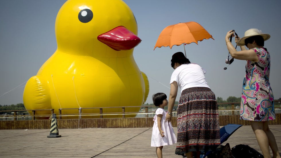 women prepare to take a souvenir photo of a child in front of a  metre high rubber duck at the nanhaizi country park in beijing on sunday photo ap: metre giant umbrella