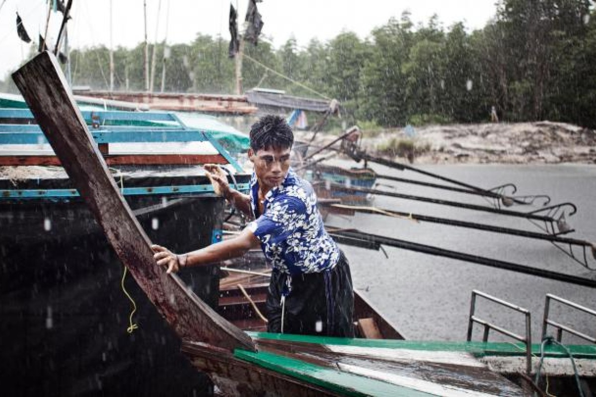 A Moken man tends to his boat during a storm in Phang Nga.