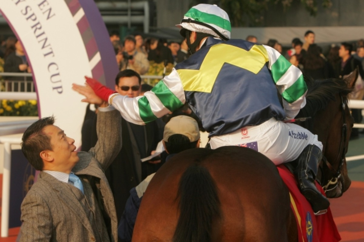 Star horse trainer Ricky Yiu high-fives with rider Brett Prebble on Sacred Kingdom at the Sha Tin Racecourse on Jan 16, 2011. Photo: SCMP/ Kenneth Chan